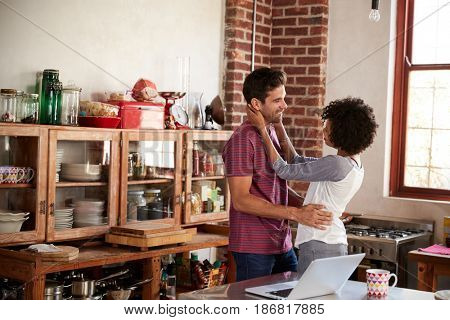 Young mixed race couple embracing in kitchen, waist up