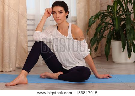 Fitness Woman Sitting At Home. Female In Sportswear Doing Meditation On Exercise On Mat In Living Ro