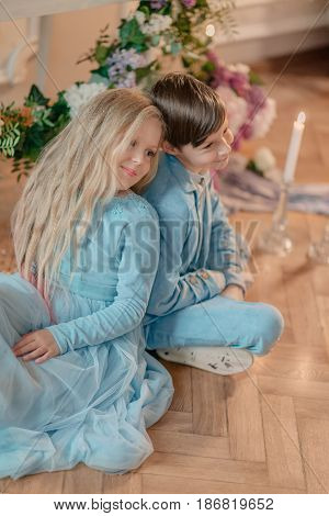 little boy and girl in a blue costume sitting on floor in Studio with flowers and candle