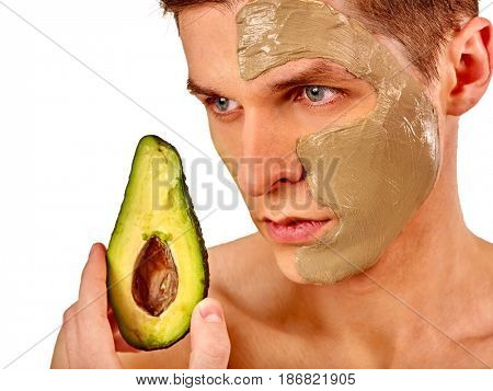 Facial mask from fresh fruits and clay for man concept. Face with treatment mud applied . Male with avocado half for skin care procedure in salon. Mask of fresh fruit helps to get rid of black spots.
