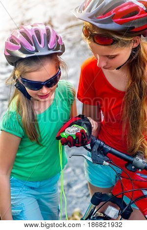 Bikes cycling girl. Children rides bicycle in cycling look at compass. Kids looking for way. People lost their way traveling unaccompanied.