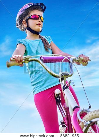 Child traveling bicycle in summer park. Girls road bike for running aganist blue sky. Cycling trip is good for health. Portrait of little girl in rainbow goggles and helmet. Bottom view.