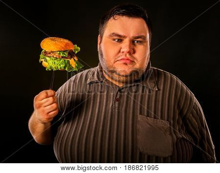 Diet failure of fat man eating fast food hamberger. Happy smile overweight person who spoiled healthy food by eating huge hamburger on fork. Junk meal leads to obesity. Refusal from harmful food.