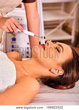 Facial massage at beauty salon. Electric stimulation skin care of woman. Equipment for microcurrent lift face. Anti aging neck non surgical treatment. Modern technologies and methods of rejuvenation.