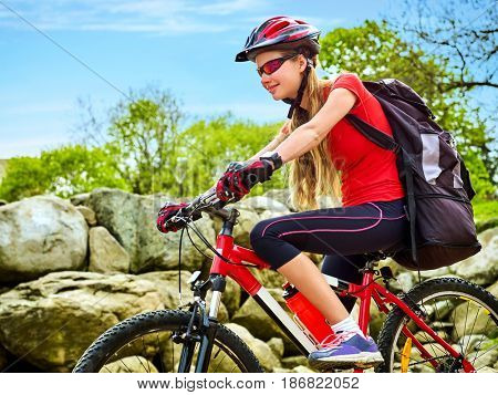 Woman on bicycle ride mountain. Girl traveling in summer park. Early morning with blue sky and clouds. Cycling person with rucksack. Sport trip is good for health. Girl is exploring new terrain .