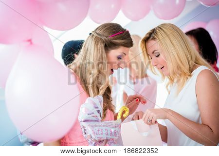 Woman giving gift to pregnant friend on baby shower party