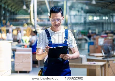 Worker in Asian production plant or factory working on checklist with clipboard