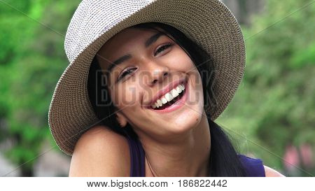 A Teenager Laughing and Wearing a Hat