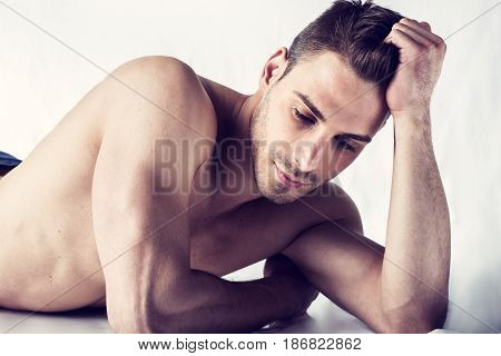 Sad expression, naked young man on white sheets looking at camera, resting on his arm