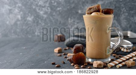 Cold milk with coffee ice on a gray background