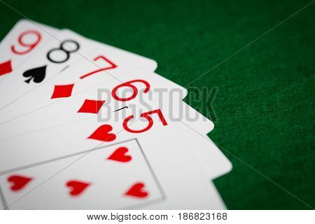 casino, gambling, games of chance, hazard and entertainment concept - straight poker hand of playing cards on green cloth
