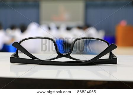 eyeglasses old or spectacles of teacher on the table in seminar conference classroom: Select focus with shallow depth of field.