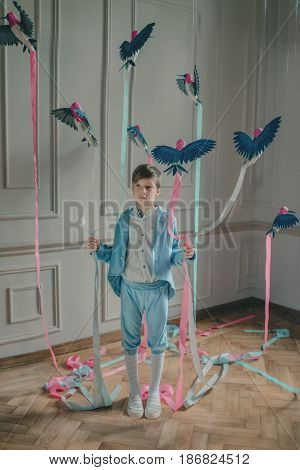 in the Studio the boy in the blue suit with birds and colored ribbons