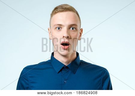 Portrait of young amazed man isolated on white