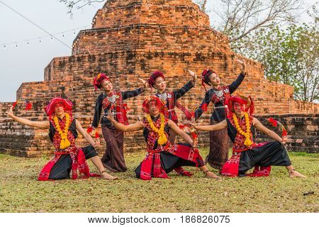 KALASIN THAILAND - FEBRUARY 20 2016: Girl and boy dancers with local dress doing Thai Northeastern traditional dance at Yaku Pagoda to celebrate Buddism event in Kalasin
