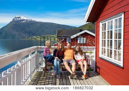 happy family on a wooden terrace with the beautiful fjord at the background