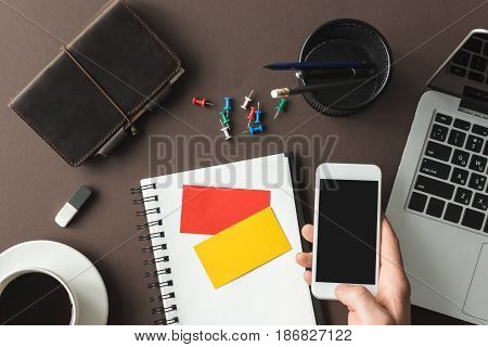 Top View Of Hand Holding Smartphone With Notebook And Stickers On Home Office Table