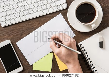 Top View Of Man Writing On Paper On Home Office Table