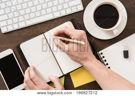 Top View Of Man Writing In Notebook On Home Office Table