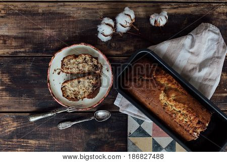 Top view of composition of artisan clay made plate with pieces of banana cake vintage cuttlery on old wooden textured table background