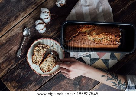 Authentic arm with tattoo set on the beautiful vintage table with antique cuttlery and hand made vegan ecologic dairy free banana bread