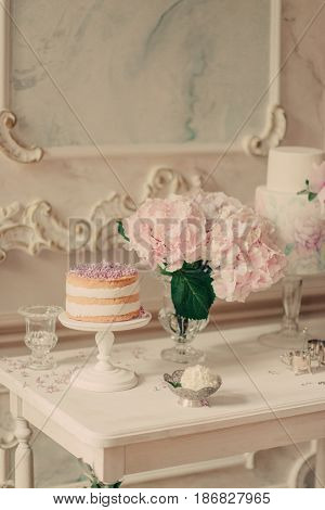 On white table vases with lilac and hydrangea cake and picture in frame