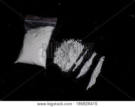 Cocaine drug powder bag, pile and lines on black background