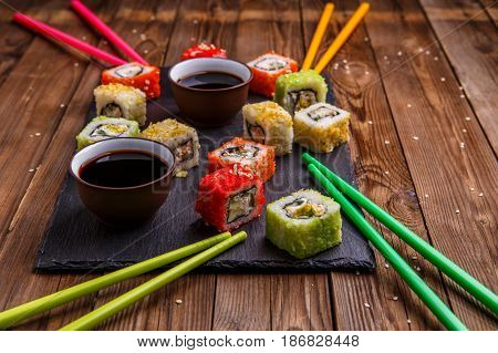 Sushi Set rolls with soy sauce served on gray stone slate on wooden background
