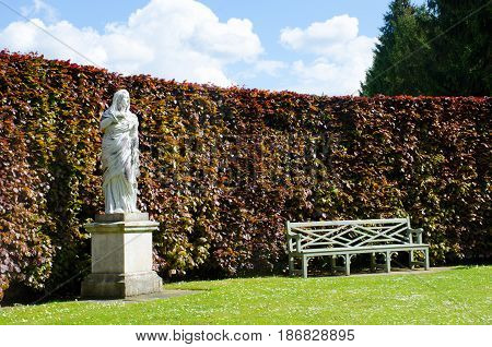 Statue with Bench in Formal English Country Garden
