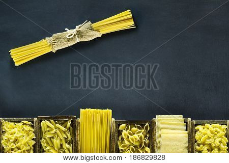 Different kind of Italian pasta in wooden boxes on a dark blue background with copy space