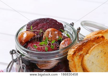 jar of baked beetroot with garlic and toasts on checkered dishtowel - close up