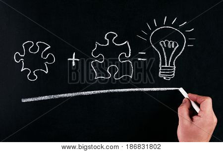 Businessmans Hand drawing puzzle on blackboard to explain business concept. Solving puzzle together. Drawing light bulb on blackboard. Combining the wisdom for developing new idea.