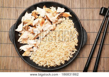 Frying pan with delicious chicken and rice on wicker mat