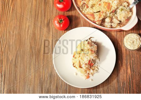 Tasty rice with chicken and vegetables on wooden table