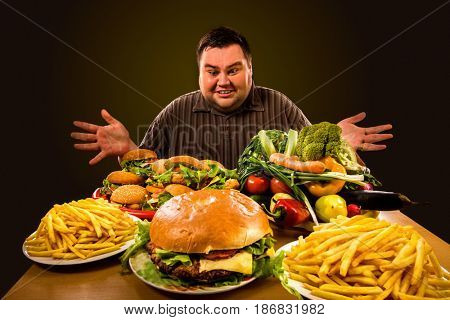 Diet fat man who makes choice between healthy and unhealthy food. Overweight male with hamburgers, french fries and vegetables trays trying to lose weight first time Dinner is field of the working day