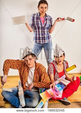 Repair group of people building home using paint roller tools. Woman and man in newspaper cap holding color guide renovation apartment.