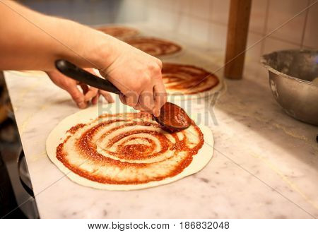 food, culinary, italian cuisine, people and cooking concept - cook with spoon applying tomato sauce to raw pizza dough at pizzeria