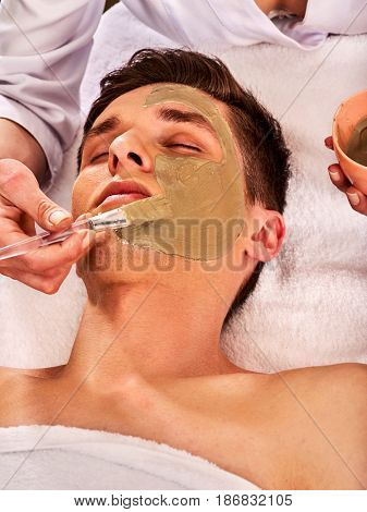 Mud facial mask of man in spa salon. Massage with clay full face. Girl on with therapy room. Man lying on spa bed. Beautician with bowl therapeutic procedure isolated background.
