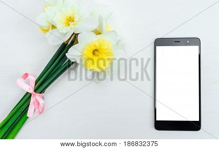 Yellow bouquet of narcissus on white wooden background. Blank card flat lay. Top view on table with narcissus and phone free space