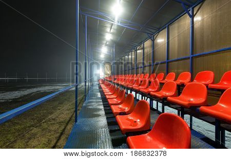 Empty tribune with rows wet red plastic seats on a football field with snow and puddles. (at night)
