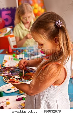 Small student girl painting in art school class. Child drawing by paints on table. Portrait of kids in kindergarten. Craft drawing education develops creative abilities of children. Children learn to