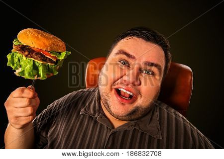 Diet failure of fat man eating fast food hamberger. Happy smile overweight person who spoiled healthy food by eating huge hamburger on fork. Junk meal leads to obesity. Man rejoices at the end of the