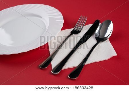 Empty white dinner plate with silver fork and Dessert Tablespoon isolated on red tablecloth background with copy space. Table Setting Folded Napkin. Dinner place setting