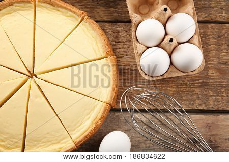 Tasty homemade cheesecake, eggs and whisk on wooden table, closeup