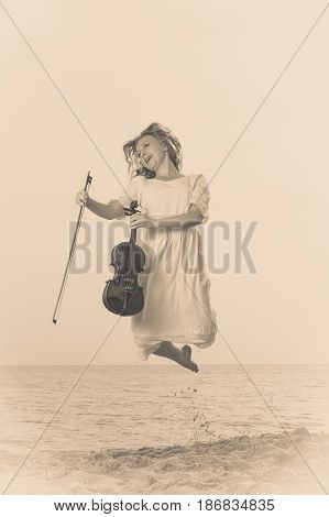 Music love hobby and everyday passion concept. Woman on beach near sea holding violin and jumping during sunset