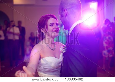 Bride Smiles Dancing With A Groom In Pink Disco Light