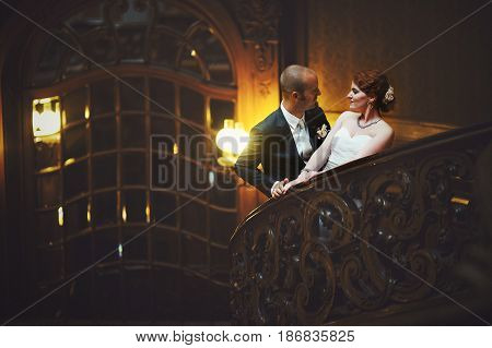 Stylish Wedding Couple Poses On The Stairs In Old Wooden Hall