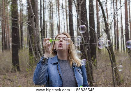 beautiful girl in spring blow bubbles in the Park area