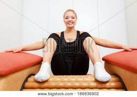 Skincare bodycare wellness concept. Woman getting rid of buttocks cellulite on big roll machine. Healthy massage treatment in spa