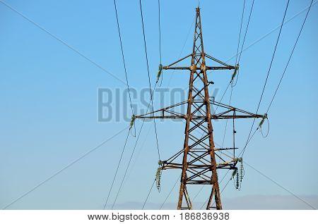 Electrical transmission pylon. High voltage. Blue sky background.
